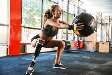 Portrait of european invalid woman with prosthesis in tracksuit, doing sit-ups with fitness ball in gym