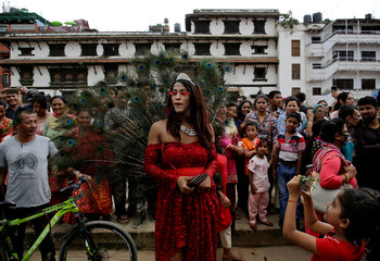 A girl takes picture of a reveller during a LGBT pride parade to mark Gaijatra Festival, also known as the festival of cows, in Kathmandu