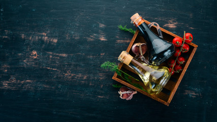 Olive oil and soy sauce in glass jars. Spices and Sauce. Top view. On a black wooden background. Free space for text.