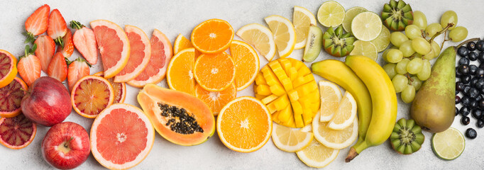 Raw fruits in rainbow colours, strawberries, mango, grapes, bananas, grapefruit on the off white table, top view, long photo, selective focus