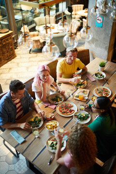 Five young friends sitting by large served wooden table and enjoying food and talk in cafe or restaurant