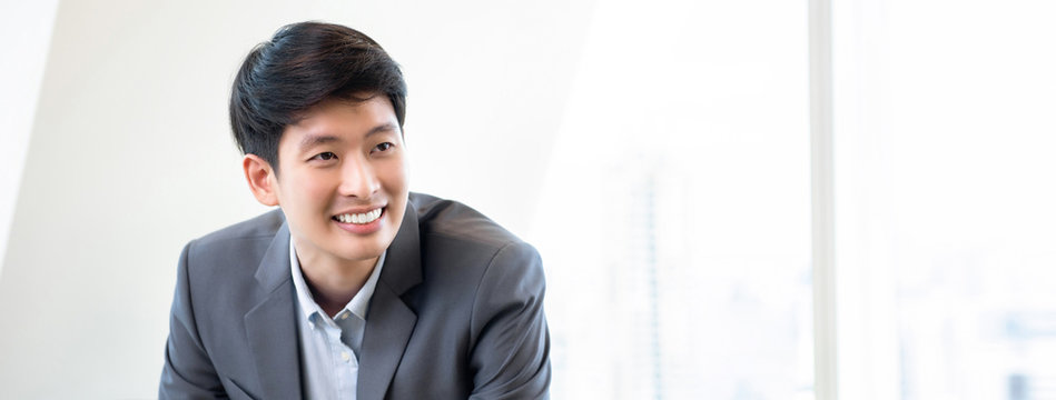 Young smiling Asian businessman in white office banner background