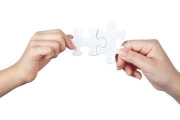 Female and child hand holding jigsaw puzzle pieces