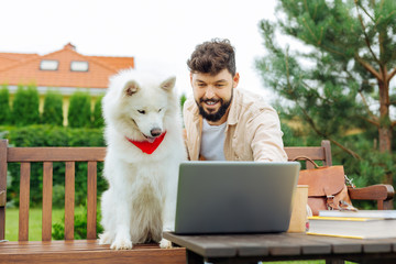 Smiling man. Bearded handsome man smiling broadly while showing photos on laptop his white dog