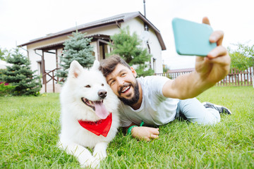 Making photo. Handsome smiling man and white fluffy husky lying on grass near summer house making photo