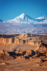 Panorama of Moon Valley in Atacama desert, snowy Andes mountain range in the background, Chile