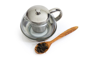 Empty glass teapot and dried tea leaves in wooden spoon