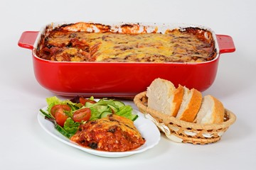 Baked layers of aubergine, cheese and tomato topped with melted cheese served with salad and bread with the remainder of the baked aubergine in a red ceramic baking dish to the rear.