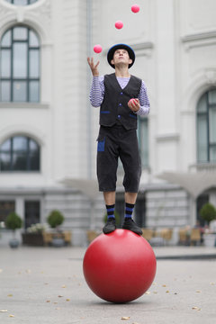 The clown and balancer juggles with pink balls , standing on a big red ball in the street of a European city