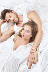 Beautiful young couple lying in bed