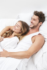 Smiling young couple relaxing in bed