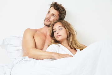 Young couple relaxing in bed in morning