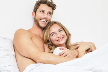 Young couple smiling in bed together