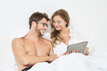 Young couple with tablet in bed, smiling
