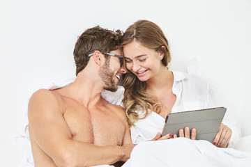 Smiling couple with tablet in bed