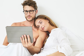 Relaxed couple sharing tablet in bed