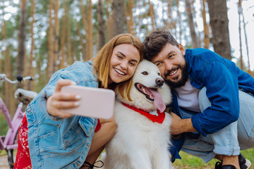 Photo with owners. Dark-eyed white dog posing for photo with his owners while walking together in the park