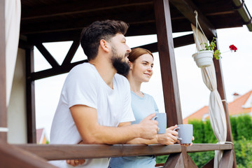 Standing on balcony. Beaming blonde-haired wife and bearded husband standing on their balcony drinking coffee