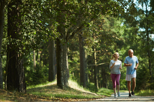 Healthy active senior couple in sportswear running among green trees on sunny day in summer