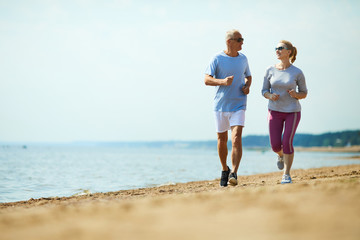 Active senior man and woman running down sandy beach with waterside on background