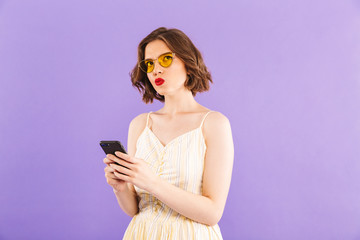 Serious woman using mobile phone isolated over purple wall background.