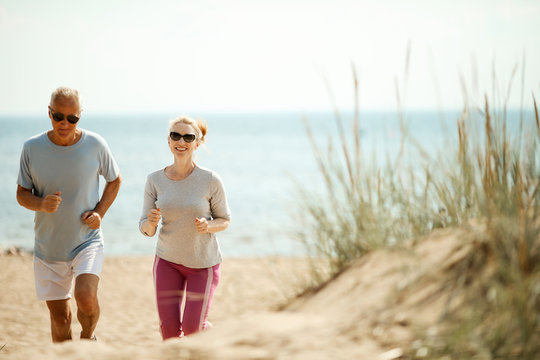 Cheerful and active couple of retired spouses jogging in the morning on the beach