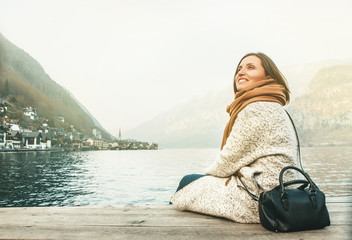 Tourist woman sits near the Hallstatt lake
