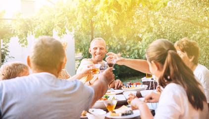 Family have dinner in summer garden