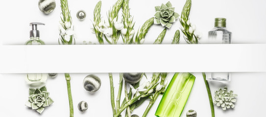 Vegan natural cosmetic and beauty concept frame. Various cosmetic products with green flowers and plants on white background Fotoväggar