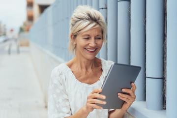 lächelnde, ältere frau steht in der stadt und schaut auf ihr tablet