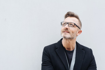 Man with glasses wearing black coat looking up
