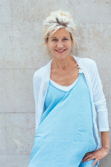 Mature blonde smiling woman wearing blue dress