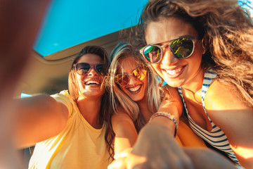Three female friends enjoying traveling in the car. Sitting in rear seat and and making selfie.