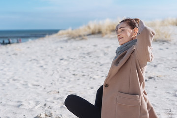 Woman spending a relaxing winter day at a beach