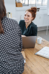 Happy young businesswoman chatting to a colleague