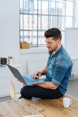 Young man holding laptop while sitting on table
