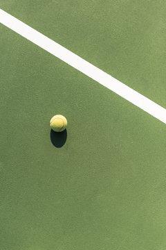 top view of tennis ball on green tennis court