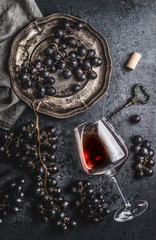 Red wine concept with glass, grapes in old plate and vintage corkscrew on dark table background, top view