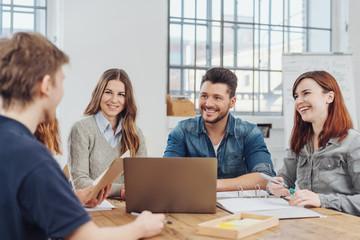 kollegen lachen in einem meeting im büro