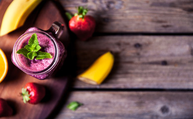 Blueberry smoothies on a wooden background with fruits. Vitamins