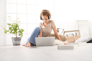 young woman with computer, headphones, smartphone and books, sitting on the floor in living room on white wide window in the background