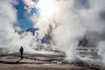 El Tatio geysers in Chile, Silhouette of a woman walking among the steams and fumaroles at sunrise