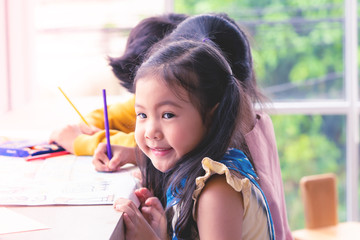Asian girl is painting on paper in Art classroom