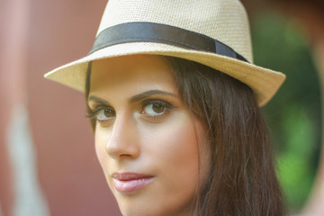 Brunette young woman closeup portrait wearing a hat and looking at camera outdoors