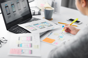 app design, technology and business concept - web designer or developer with sketches and laptop computer working on user interface at office