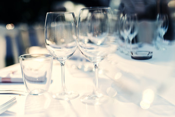 Wine glasses on dining table. Preparation for guests.