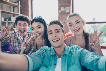 Close up portrait of cheerful youngsters make selfie on front camera of smartphone and show v-sign stand in casual wear