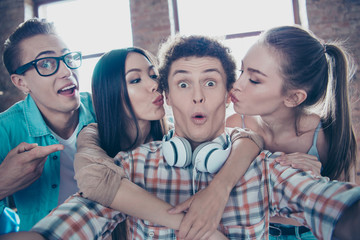 Close up portrait of cheerful youngsters make a selfie on front of the smartphone girls in casual wear kiss the guy on the cheek plump and pouted lips