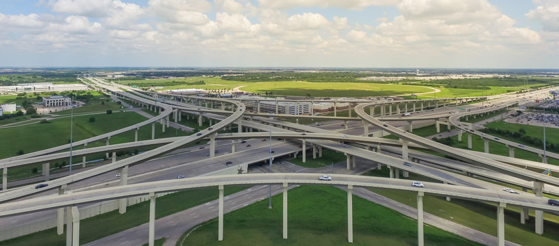 Panorama horizontal aerial Interstate 10 or Katy freeway massive intersection, stack interchange, elevated road junction overpass cloud blue sky. Top view metropolitan area of Katy, Texas, USA