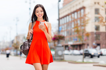Portrait of charming and lovely Asian model with backpack on the shoulder and smartphone in hand walk through the sunny city in summer day